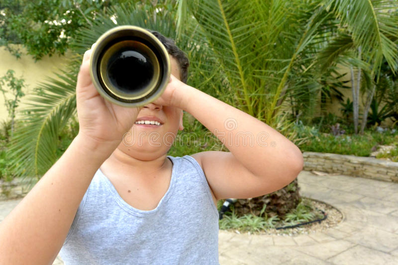 Un muchacho con el catalejo imagenes de archivo