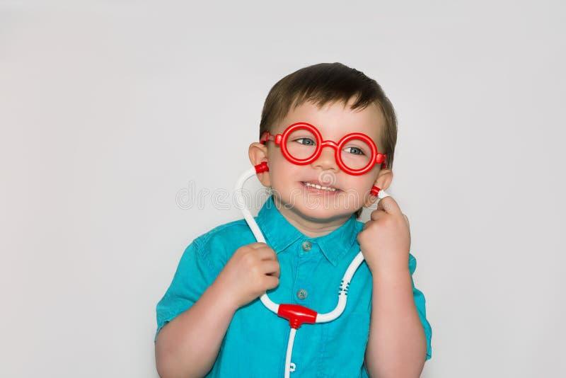 Un muchacho con el pequeño doctor de los vidrios fotografía de archivo