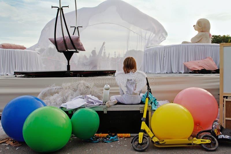 Un muchacho con las alas del ángel sienta y mira funcionamiento en el ` brillante de la gente del ` del festival en el parque Gor foto de archivo