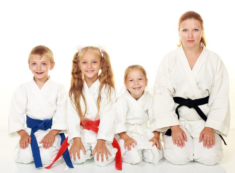 Un muchacho con su hermana y la madre con su hija que se sienta en un karate plantean ritual fotografía de archivo libre de regalías