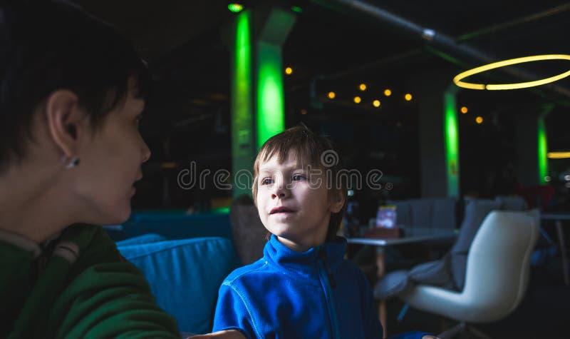 Un muchacho con su madre en un café fotografía de archivo