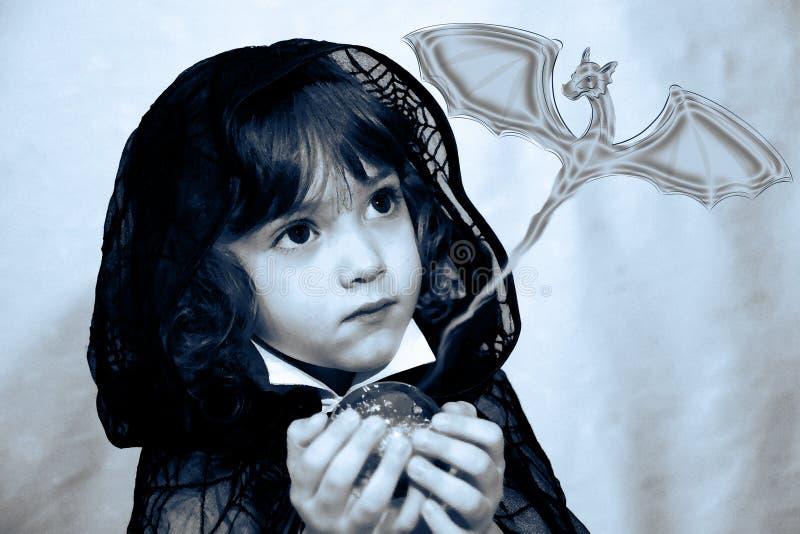 un muchacho con una bola mágica en ropa negra con una web hecha punto y un dragón gris que vuela fotos de archivo libres de regalías