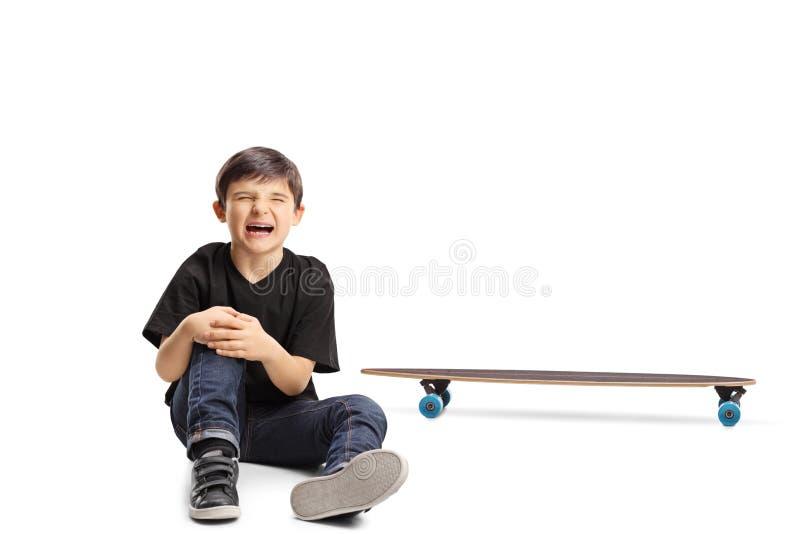 Un muchacho con una rodilla herida que se sienta al lado de un longboard fotografía de archivo