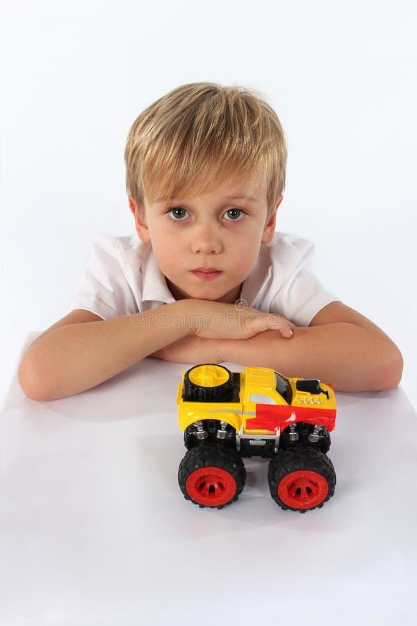 Un muchacho confiado del niño que juega con un juguete del coche imagenes de archivo