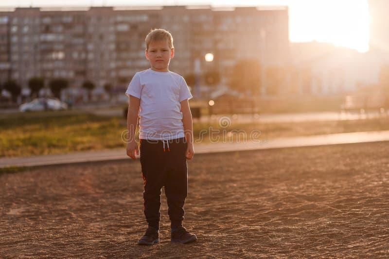 Un muchacho contrariedad en una camiseta blanca en miradas completas del crecimiento en la cámara en la luz de la puesta del sol foto de archivo