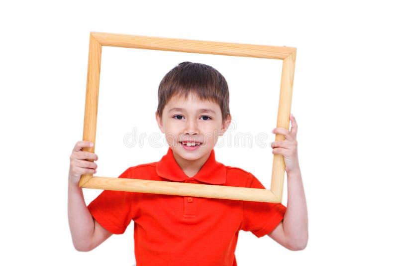 Un muchacho de 6 y.o. con un marco imagenes de archivo