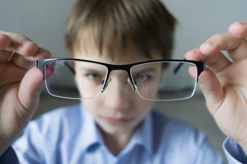 Un muchacho de 9 años en una camisa azul con los vidrios comprueba su vista Descontentado con el hecho que prescribió los vidrios imagen de archivo libre de regalías