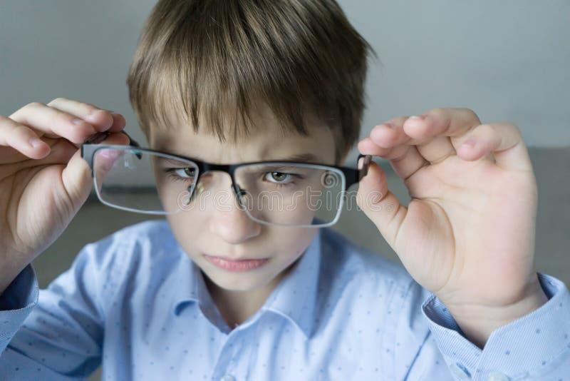 Un muchacho de 9 años en una camisa azul con los vidrios comprueba su vista Descontentado con el hecho que prescribió los vidrios fotografía de archivo libre de regalías