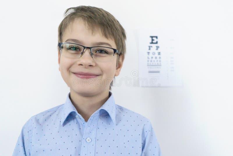 Un muchacho de 9 años en una camisa azul con los vidrios comprueba su vista Usted debe llevar los vidrios Atención sanitaria del  imágenes de archivo libres de regalías