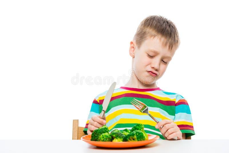 Un muchacho de 10 años mira el bróculi en una placa en repugnancia, retrato se aísla en un blanco imagenes de archivo