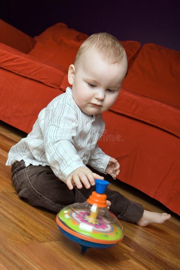 Un muchacho de los años que juega con su tapa de giro. foto de archivo