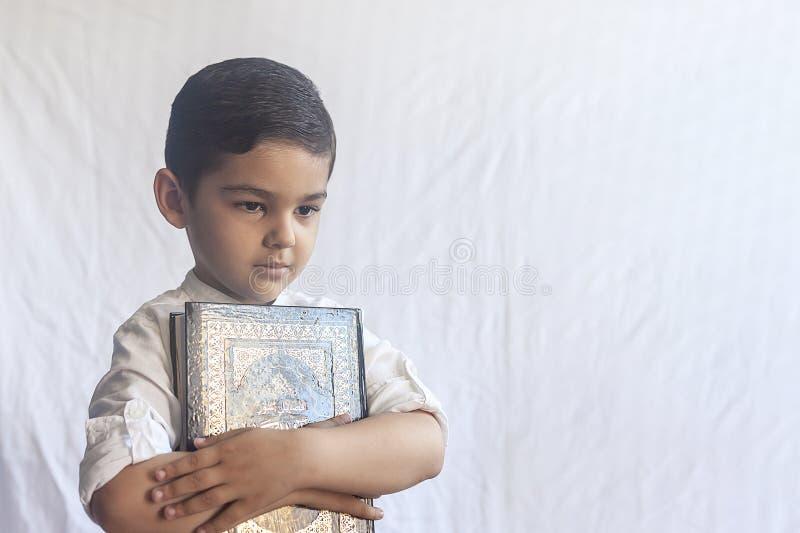 Un muchacho de Oriente Medio joven con el Quran santo Retrato de 5 años del niño musulmán que sostiene un Quran santo con el fond imagenes de archivo