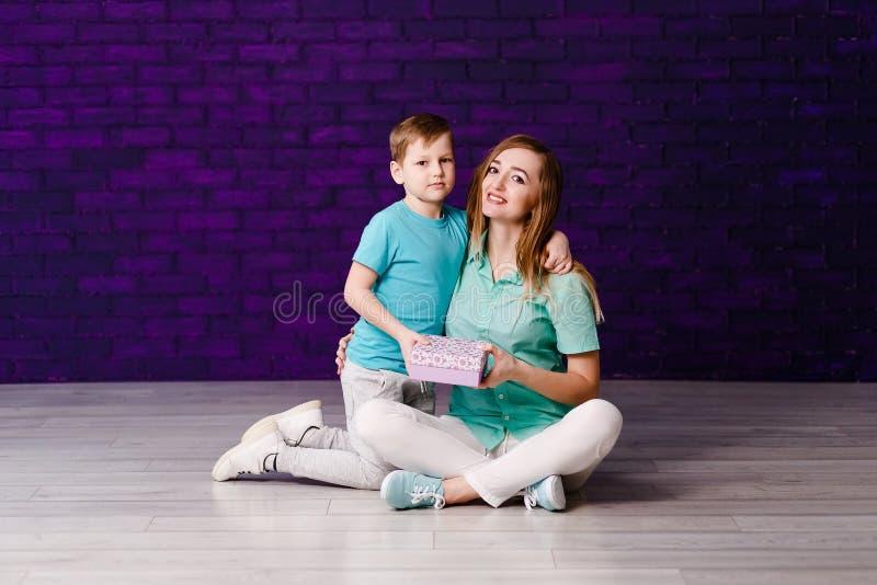 Un muchacho de siete años abraza a una madre joven hermosa fotografía de archivo libre de regalías