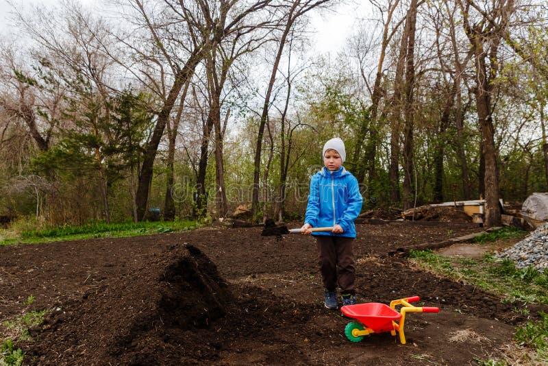 Un muchacho de siete años en una cazadora azul y un sombrero lanza la tierra con una pala del bombero en un carro en el jardín imágenes de archivo libres de regalías