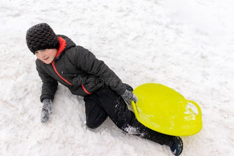 Un muchacho de siete años que mienten en la nieve y que sostienen un trineo plástico verde en su mano Concepto de actividades del foto de archivo libre de regalías