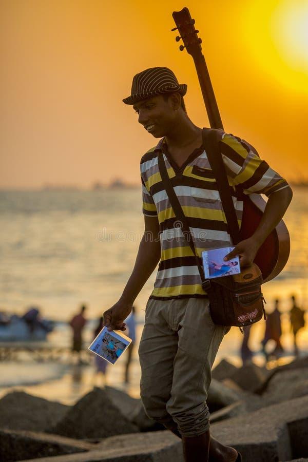 Un muchacho del fotógrafo entregó sus fotografías de los clientes en la playa de Patenga, Chittagong, Bangladesh fotografía de archivo