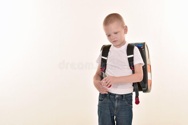 Un muchacho elemental caucásico de la edad que presenta en uniforme y baccpack aislado en el fondo blanco Escuela y concepto de l foto de archivo libre de regalías