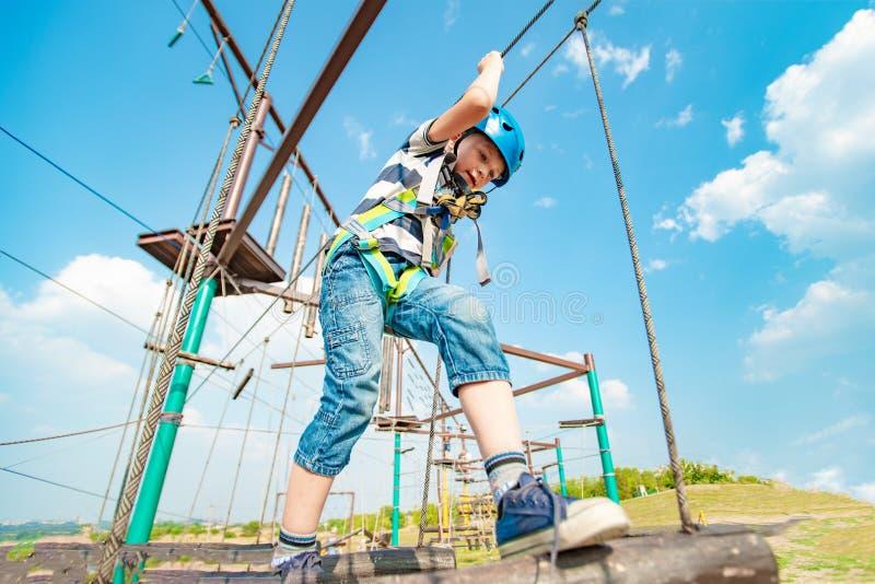 Un muchacho en un camino de la cuerda supera obstáculos en un parque extremo imagen de archivo