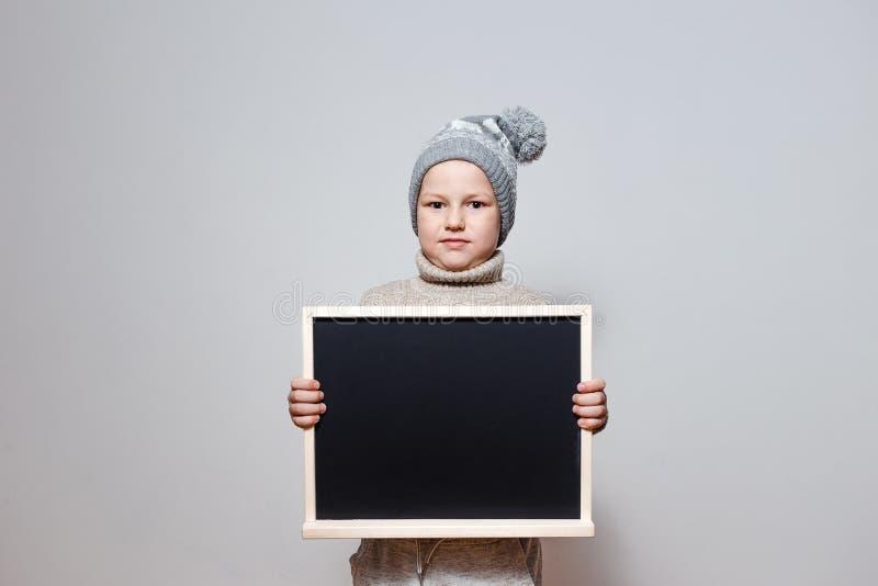 Un muchacho en un suéter y un sombrero que sostienen una tábula rasa en un fondo blanco fotografía de archivo libre de regalías