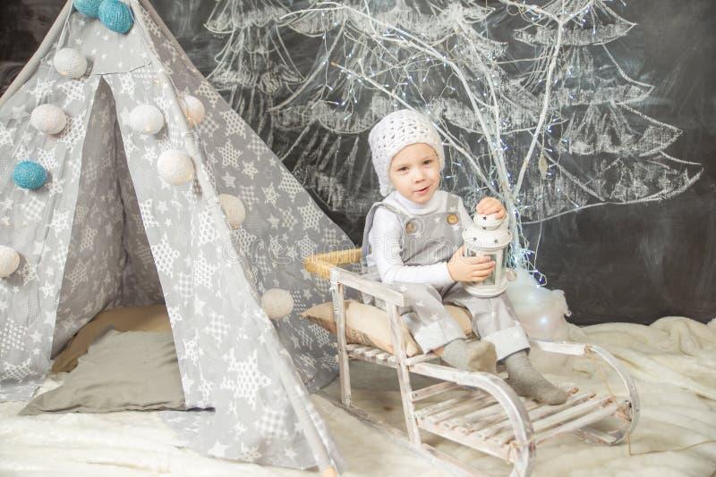 Un muchacho en un traje blanco se sienta en una tienda foto de archivo