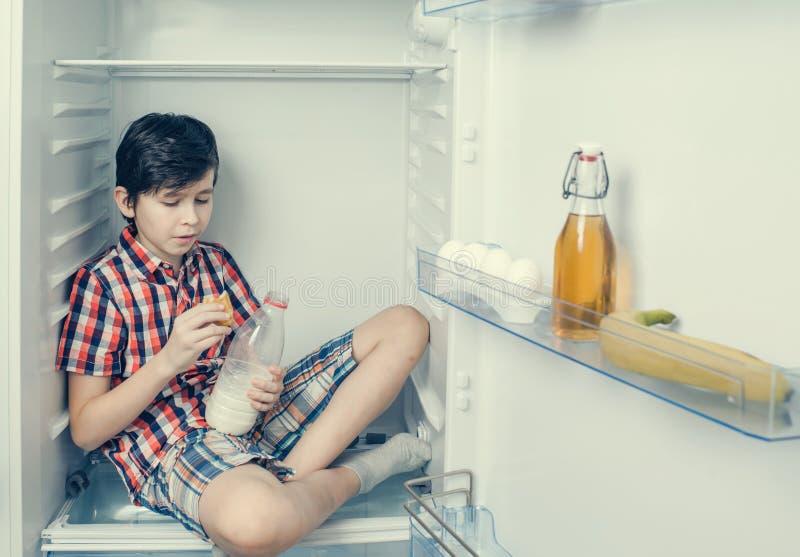 Un muchacho en una camisa y los pantalones cortos que comen un cruasán y una bebida ordeñan dentro de un refrigerador con la comi fotografía de archivo