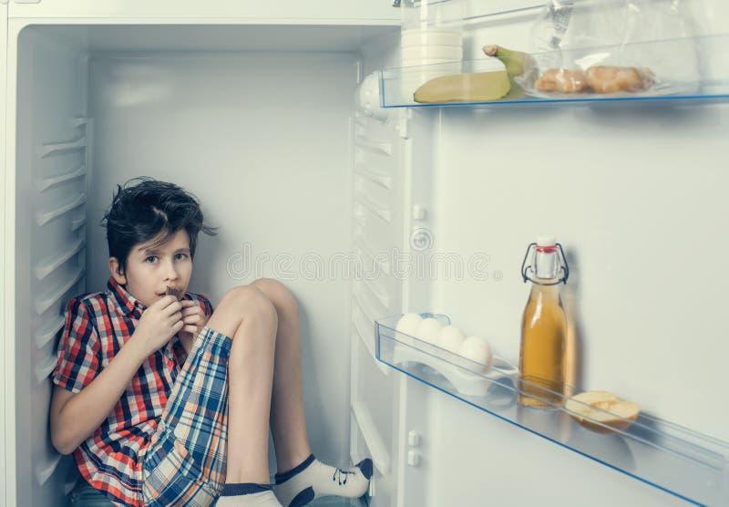 Un muchacho en una camisa y pantalones cortos que come una barra de chocolate dentro de un refrigerador con la comida fotos de archivo