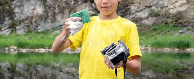 Un muchacho en una camiseta amarilla sostiene una cámara en su mano sin una lente y una esponja con el jabón Equipo fotográfico d imagenes de archivo
