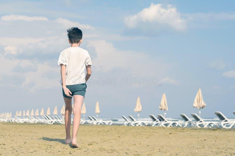 Un muchacho en una camiseta y paseos de los pantalones cortos en la playa arenosa de Mackenzie en Larnaca chipre foto de archivo libre de regalías