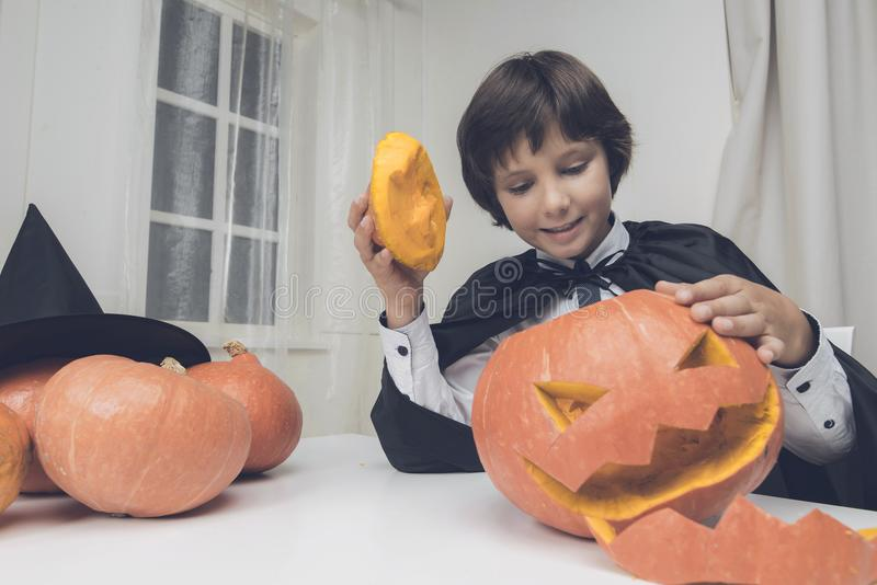 Un muchacho en una capa negra admira una calabaza que él acaba de cortar para Halloween imágenes de archivo libres de regalías