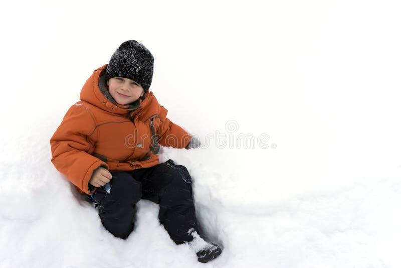Un muchacho en una chaqueta anaranjada y un sombrero negro en un día de invierno que se sienta en una nieve acumulada por la vent fotografía de archivo
