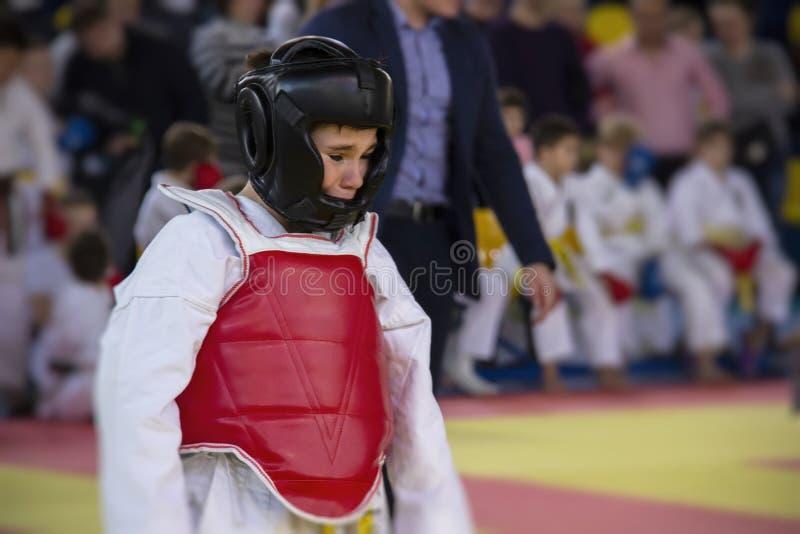 Un muchacho en una competencia del karate del kimono está llorando porque él perdió la lucha y fue herido imágenes de archivo libres de regalías