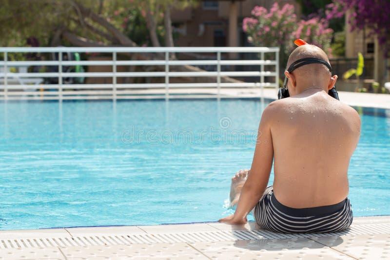 Un muchacho en una piscina con una máscara para bucear imagen de archivo libre de regalías