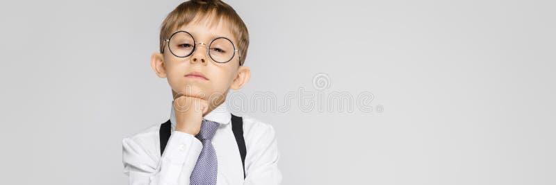 Un muchacho encantador en una camisa blanca, ligas, un lazo y vaqueros de la luz se coloca en un fondo gris El muchacho puso su b imagen de archivo