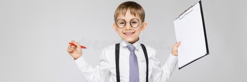 Un muchacho encantador en una camisa blanca, ligas, un lazo y vaqueros de la luz se coloca en un fondo gris El muchacho sostiene  imagenes de archivo
