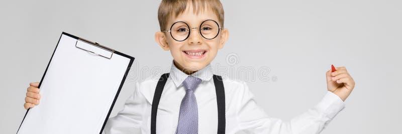 Un muchacho encantador en una camisa blanca, ligas, un lazo y vaqueros de la luz se coloca en un fondo gris El muchacho sostiene  fotos de archivo libres de regalías