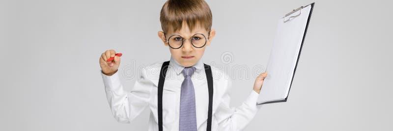 Un muchacho encantador en una camisa blanca, ligas, un lazo y vaqueros de la luz se coloca en un fondo gris El muchacho sostiene  fotografía de archivo
