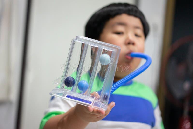 Un muchacho es de prueba y de administración de los pulmones con un secador de la tri bola foto de archivo