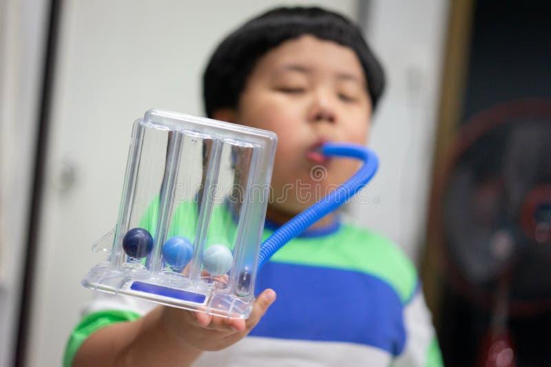 Un muchacho es de prueba y de administración de los pulmones con un secador de la tri bola imagen de archivo libre de regalías