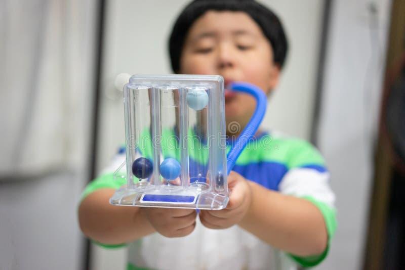 Un muchacho es de prueba y de administración de los pulmones con un secador de la tri bola imagen de archivo
