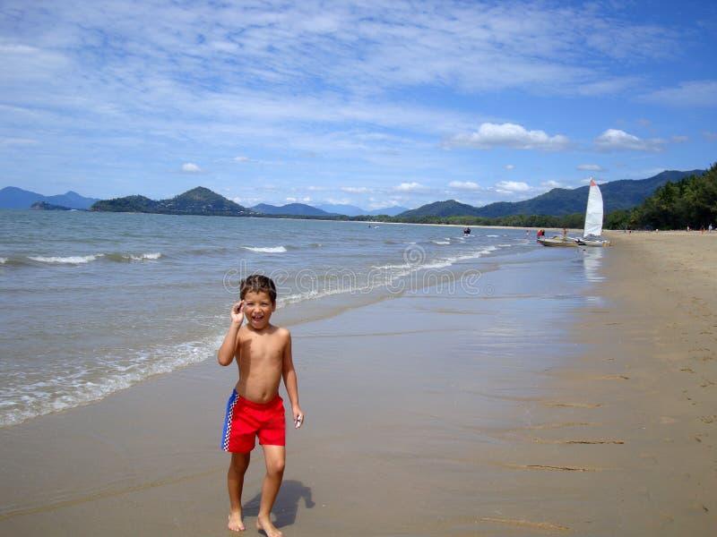 Un muchacho está caminando a lo largo de la playa hermosa de la costa australiana foto de archivo