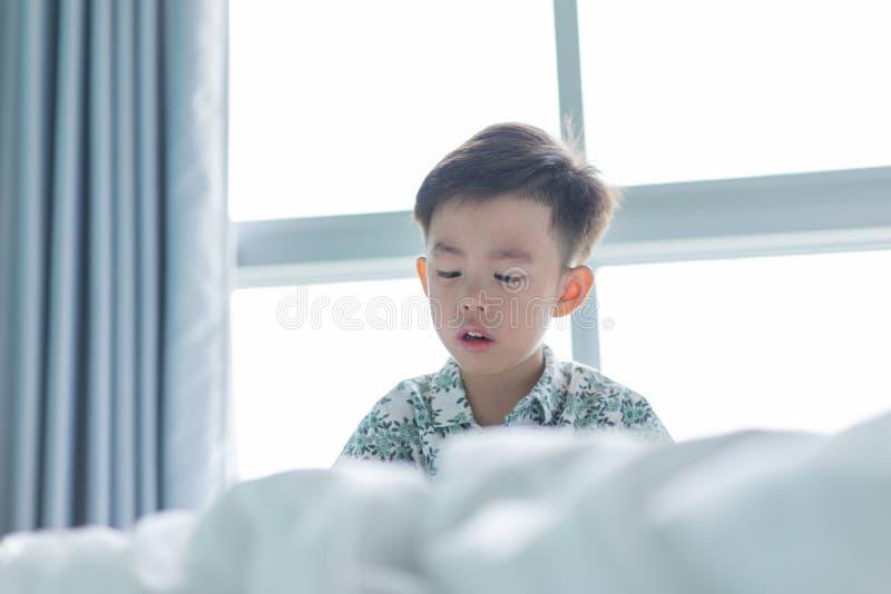 Un muchacho está jugando el juguete en el malo foto de archivo
