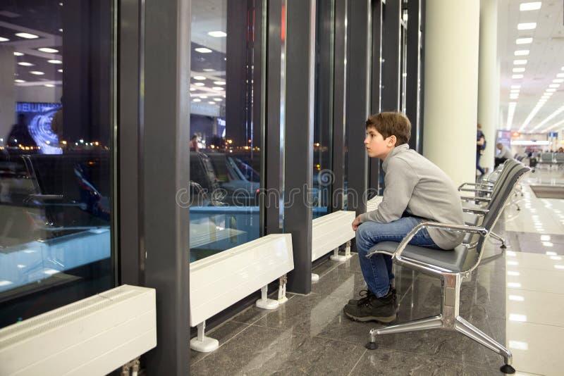 Un muchacho está localizando en el pasillo del aeropuerto fotos de archivo
