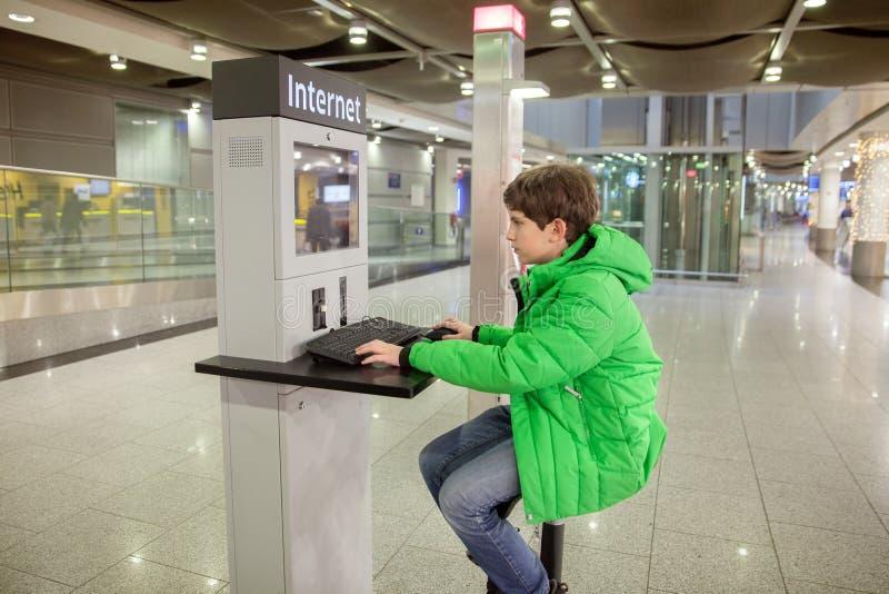 Un muchacho está trabajando en el ordenador en aeropuerto foto de archivo