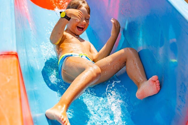 Un muchacho feliz en el tobogán acuático en una piscina que se divierte durante vacaciones de verano en aguamarina hermosa parque fotografía de archivo libre de regalías