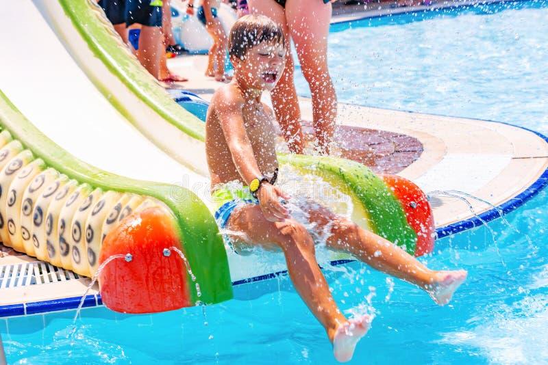 Un muchacho feliz en el tobogán acuático en una piscina que se divierte durante vacaciones de verano en aguamarina hermosa parque imagenes de archivo