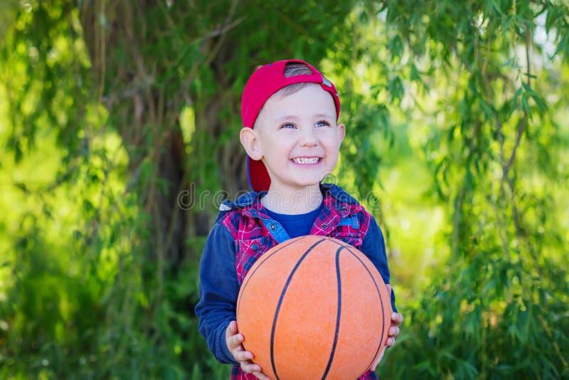 Un muchacho feliz que da un baloncesto, foto de archivo libre de regalías