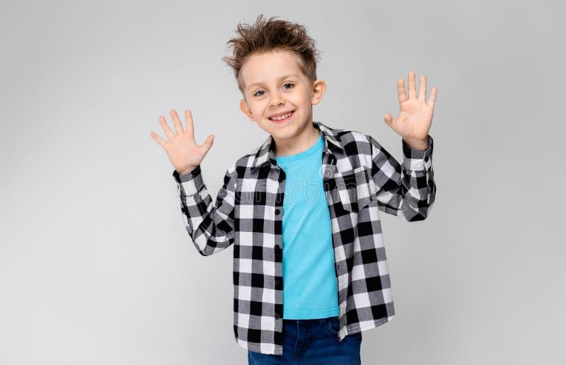 Un muchacho hermoso en una camisa de tela escocesa, camisa azul y vaqueros se coloca en un fondo gris El muchacho dobló sus brazo foto de archivo libre de regalías