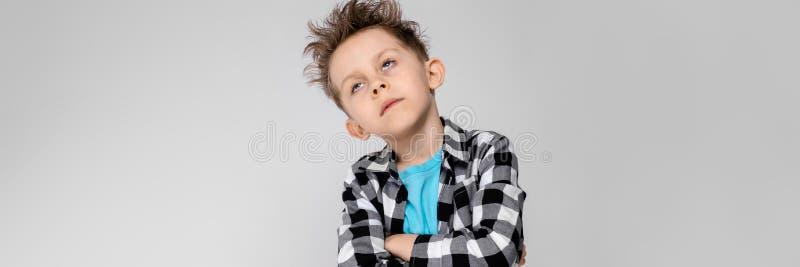 Un muchacho hermoso en una camisa de tela escocesa, camisa azul y vaqueros se coloca en un fondo gris El muchacho dobló sus brazo imagenes de archivo