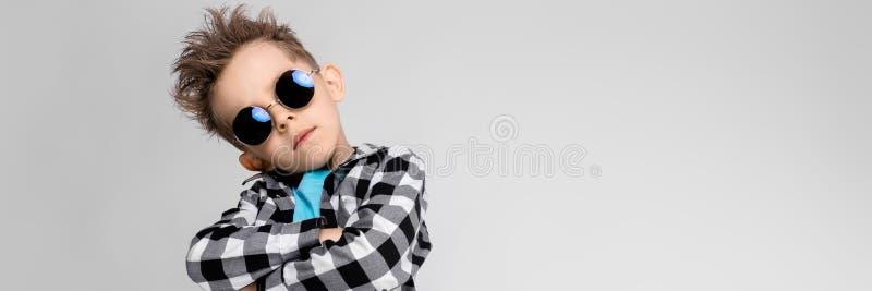 Un muchacho hermoso en una camisa de tela escocesa, camisa azul y vaqueros se coloca en un fondo gris El muchacho está llevando a imagen de archivo libre de regalías