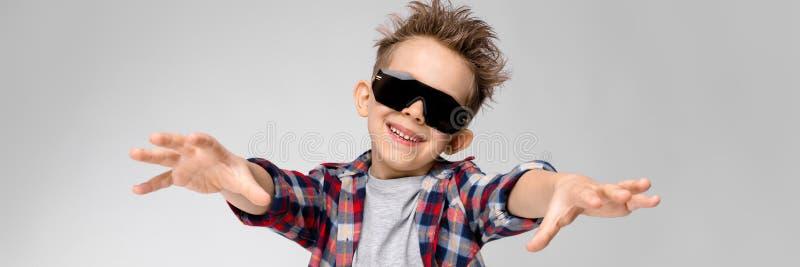 Un muchacho hermoso en una camisa de tela escocesa, camisa gris y vaqueros se coloca en un fondo gris El muchacho en lentes de so fotografía de archivo libre de regalías